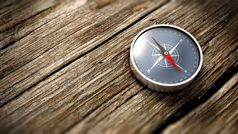 Close up compass showing north on a wooden table. 3D Rendering